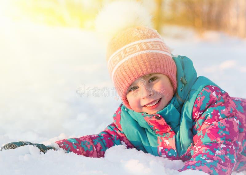 逗人喜爱的小女孩在雪有启发性太阳说谎 免版税库存照片
