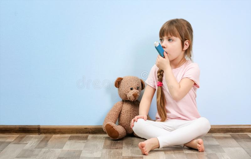 逗人喜爱的小女孩坐地板,当使用吸入器时 免版税库存图片