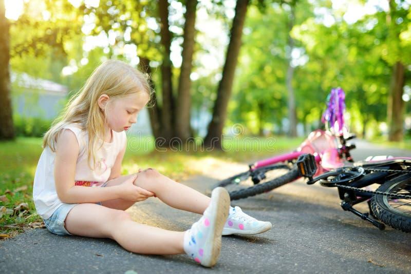 逗人喜爱的小女孩坐地面在落她的自行车在夏天公园以后 受到伤害的孩子,当骑自行车时 库存图片