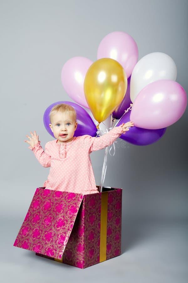 逗人喜爱的小女孩坐有气球的箱子 免版税库存照片