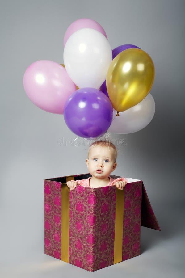 逗人喜爱的小女孩坐有气球的箱子 免版税图库摄影