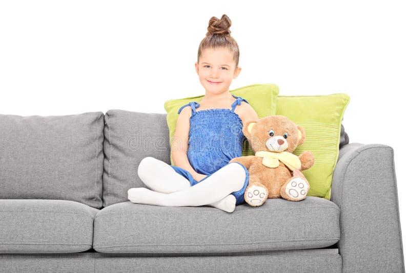 逗人喜爱的小女孩坐有玩具熊的长沙发 库存图片