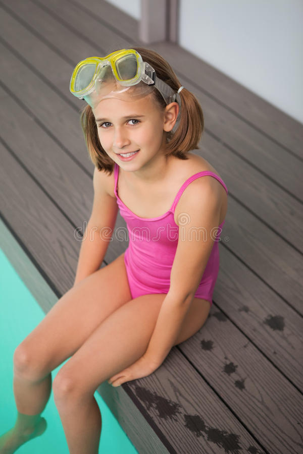 逗人喜爱的小女孩坐的游泳池边 免版税库存图片