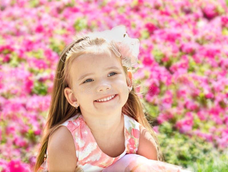 逗人喜爱的小女孩室外画象在花附近的 图库摄影