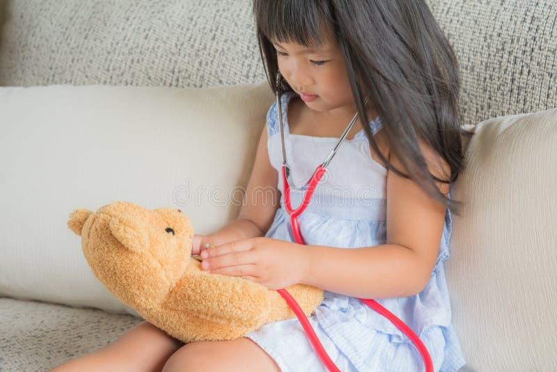 逗人喜爱的小女孩扮演有听诊器的医生 库存图片