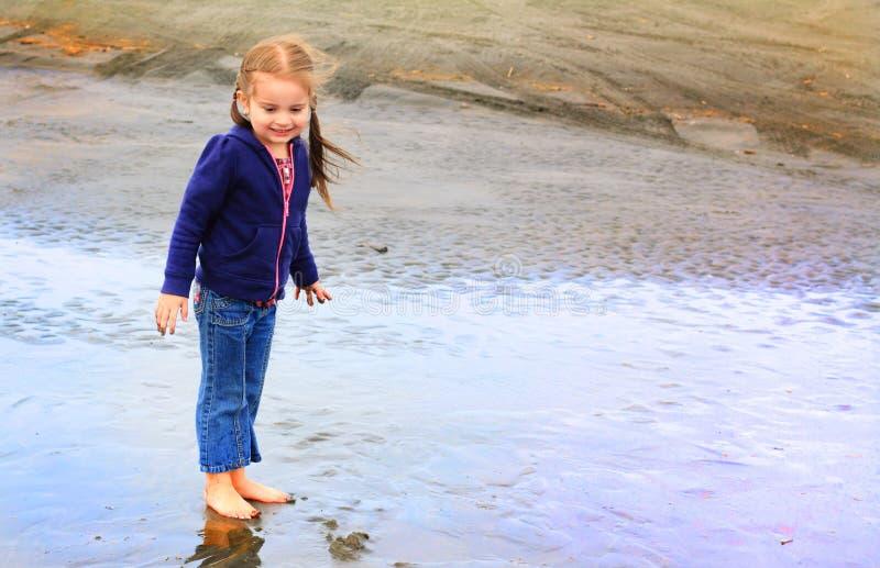 逗人喜爱的小女孩探索海滩 免版税库存图片