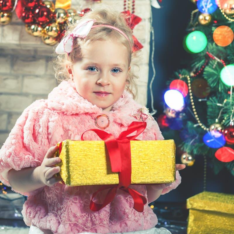 逗人喜爱的小女孩接受一棵礼物近的装饰的圣诞树 免版税库存照片