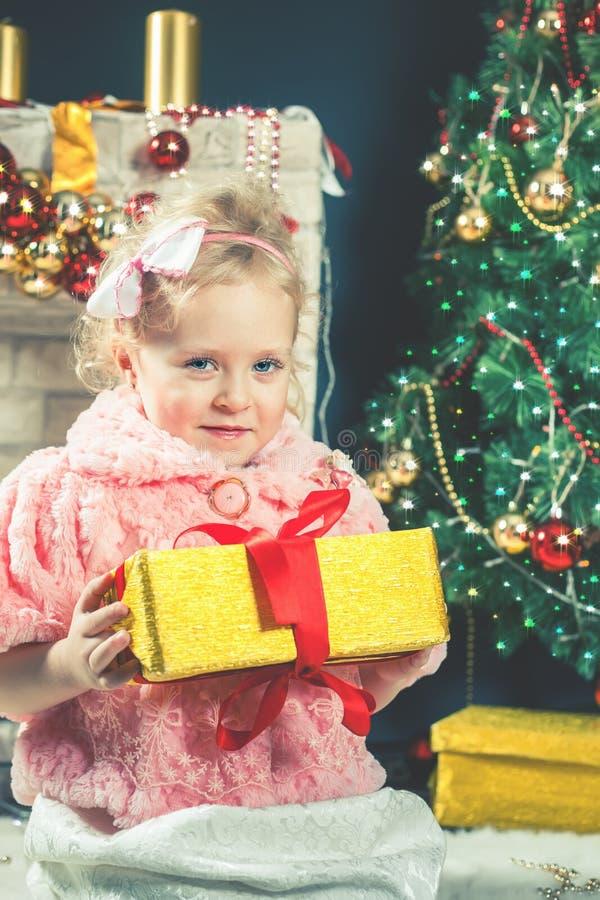 逗人喜爱的小女孩接受一棵礼物近的装饰的圣诞树 库存图片
