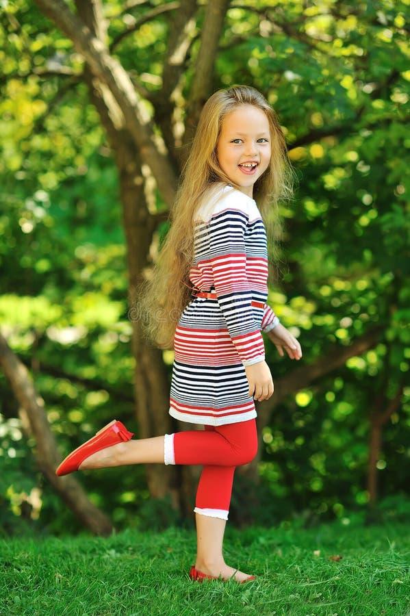 逗人喜爱的小女孩摆在夏天绿色公园的-画象 免版税库存图片