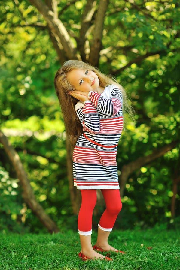 逗人喜爱的小女孩摆在夏天绿色公园的-画象 库存图片