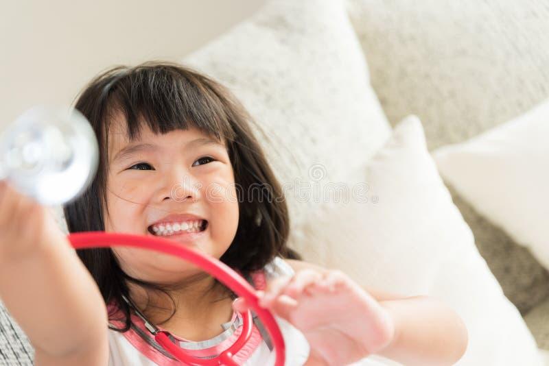 逗人喜爱的小女孩是微笑和扮演有听诊器的医生 库存图片