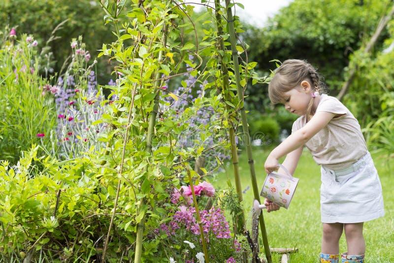 逗人喜爱的小女孩浇灌的花在庭院里 免版税库存图片