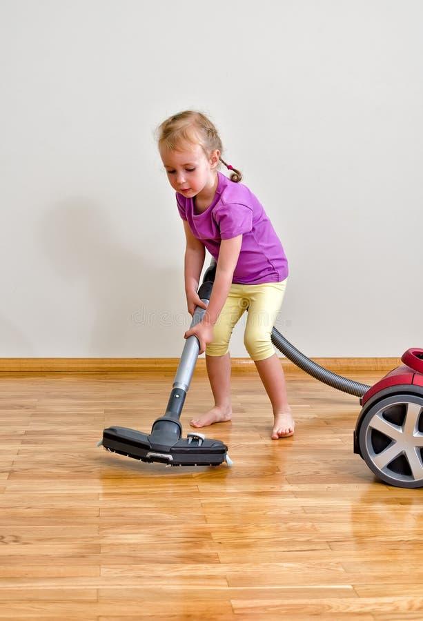 逗人喜爱的小女孩清洁楼层 库存图片