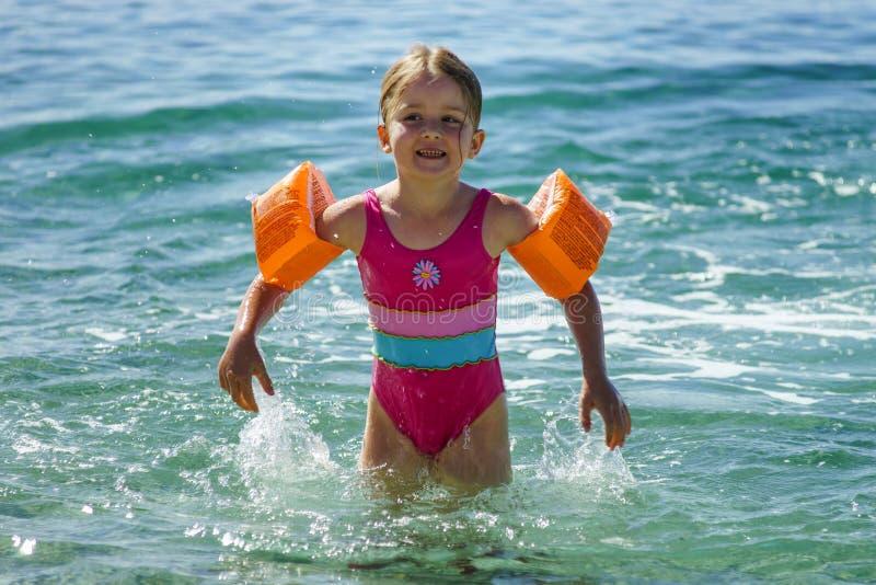 逗人喜爱的小女孩游泳在有浮水圈的海,童年概念