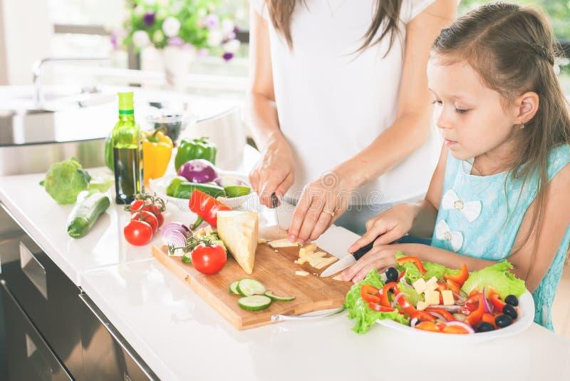 逗人喜爱的小女孩烹调与她的母亲的,健康食物 免版税库存照片
