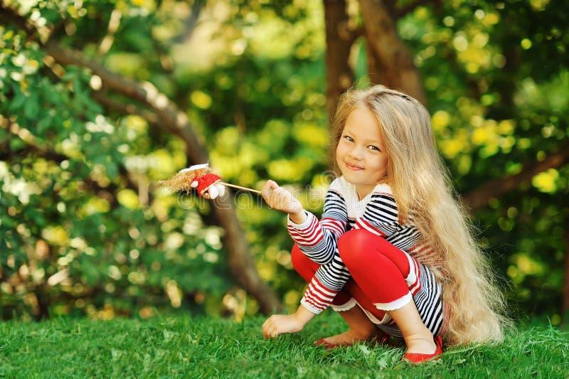 逗人喜爱的小女孩照片坐绿草 免版税库存图片
