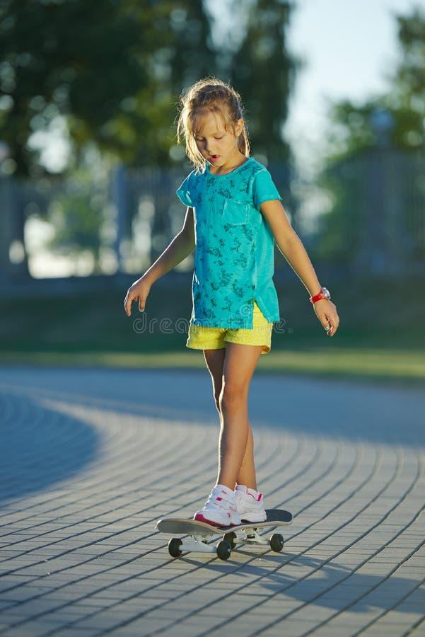 逗人喜爱的小女孩照片有滑板的 免版税库存照片