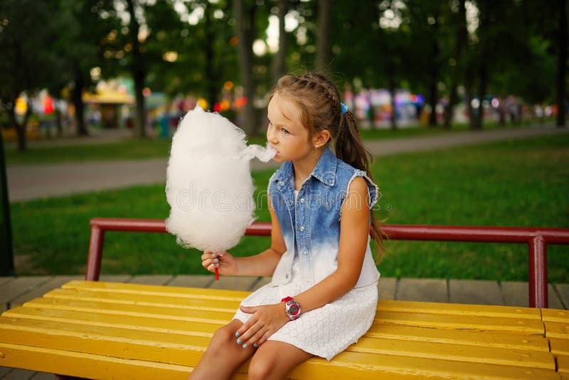 逗人喜爱的小女孩用棉花糖在公园 免版税库存照片