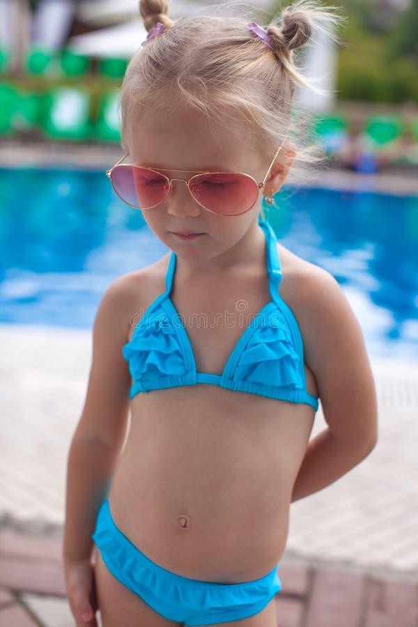 逗人喜爱的小女孩站立的单独近的游泳池 免版税库存图片