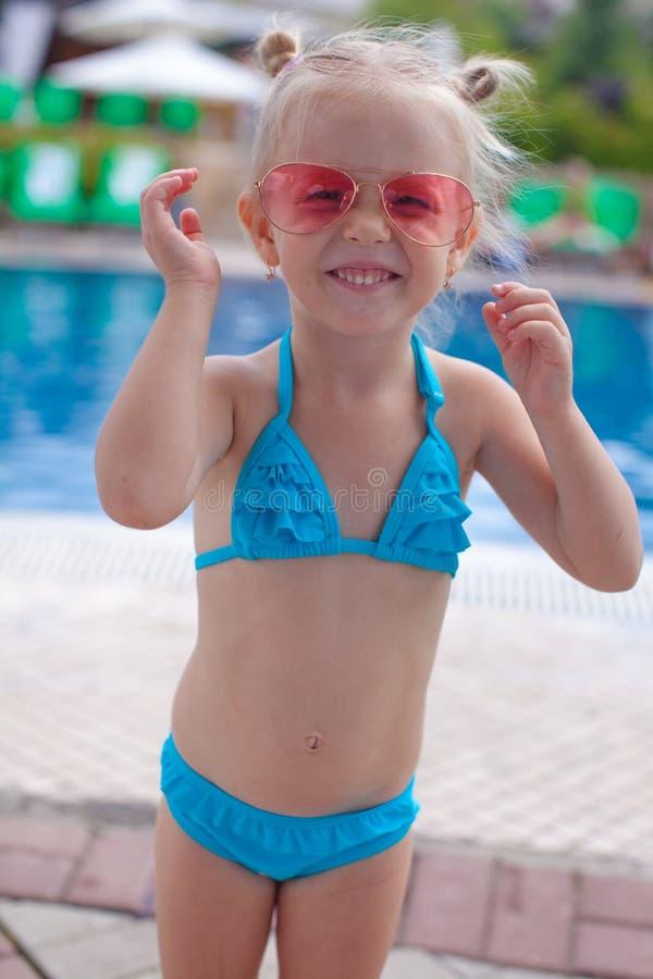 逗人喜爱的小女孩站立的单独近的游泳池 免版税库存照片