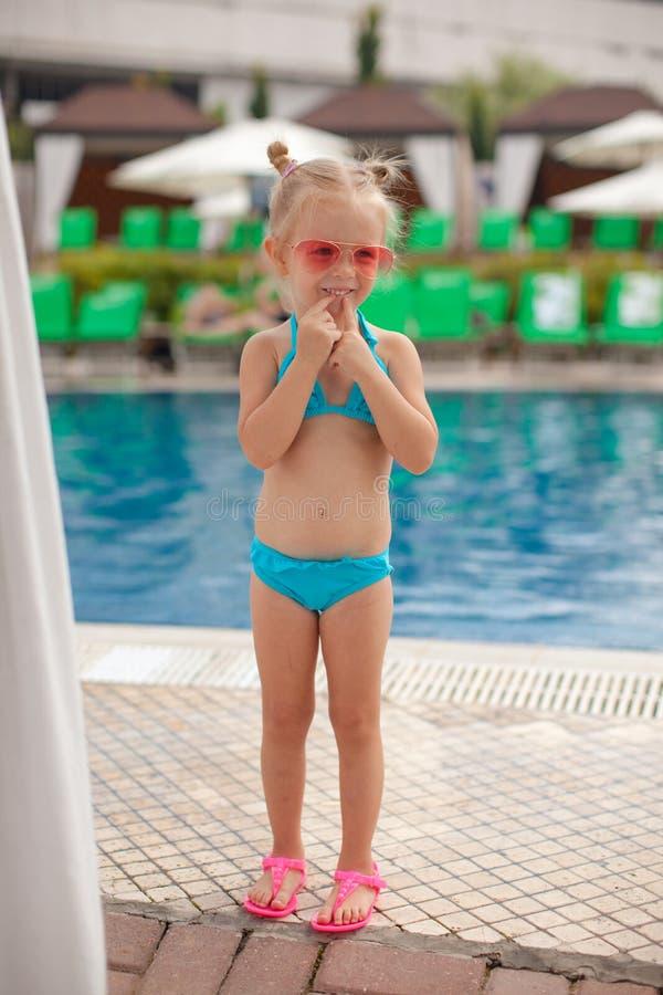 逗人喜爱的小女孩站立的单独近的游泳池 库存照片