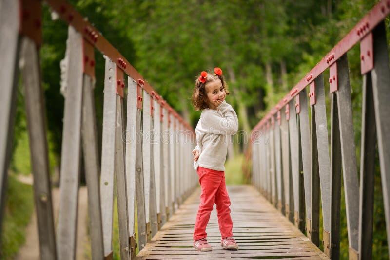 逗人喜爱的小女孩获得乐趣在一座农村桥梁 免版税库存图片