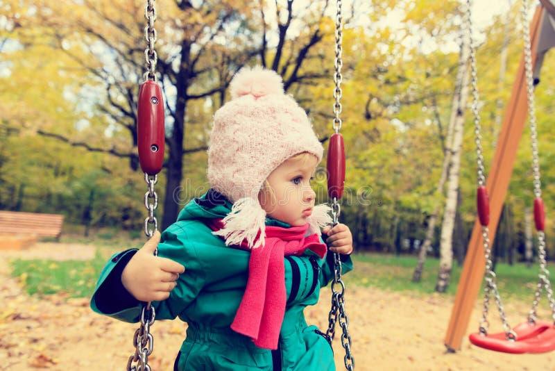 逗人喜爱的小女孩获得在摇摆的乐趣秋天 免版税库存照片