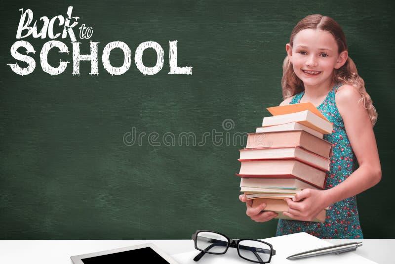 逗人喜爱的小女孩运载的书的综合图象在图书馆里 免版税库存图片