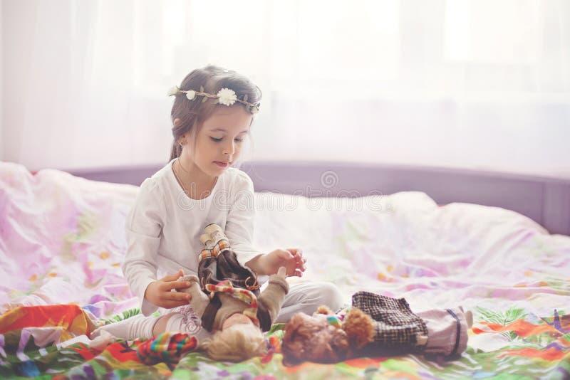 逗人喜爱的小女孩,在家使用与玩偶在床上 免版税库存照片