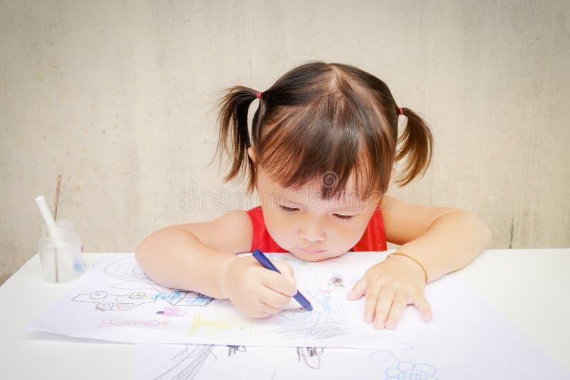 逗人喜爱的小女孩画与在幼儿园,无限的无边的想象力的蜡笔通过五颜六色:孩子 免版税库存照片