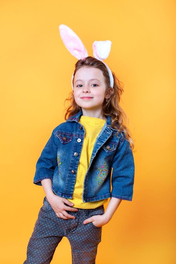 逗人喜爱的小孩佩带的兔宝宝耳朵在橙色背景的复活节天 免版税库存图片