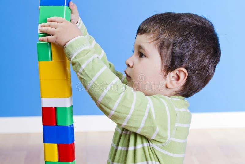 逗人喜爱的小孩使用与玩具,当坐地板时 免版税库存图片