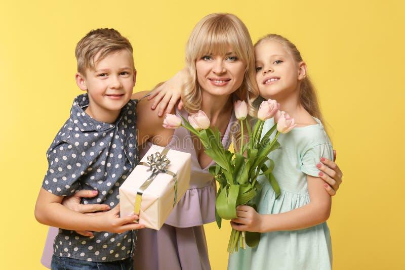 逗人喜爱的小孩和他们的母亲画象有礼物的在颜色背景 免版税库存照片