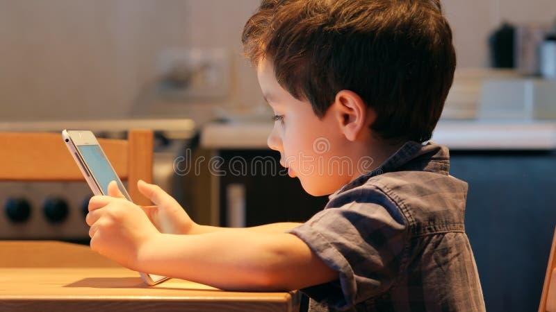 逗人喜爱的小孩在家使用一台片剂个人计算机在桌 便衣 侧视图 库存图片