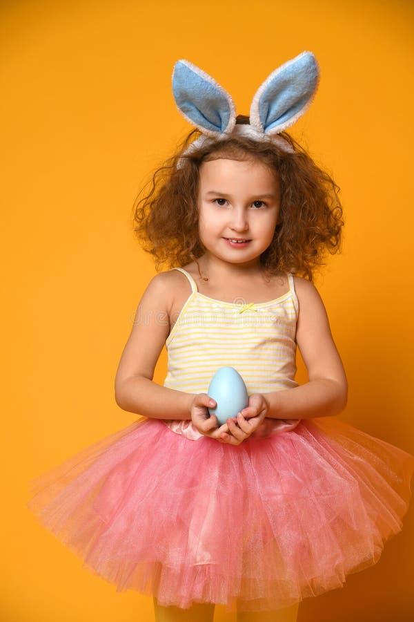 逗人喜爱的小孩女孩佩带的兔宝宝耳朵在复活节天 免版税图库摄影