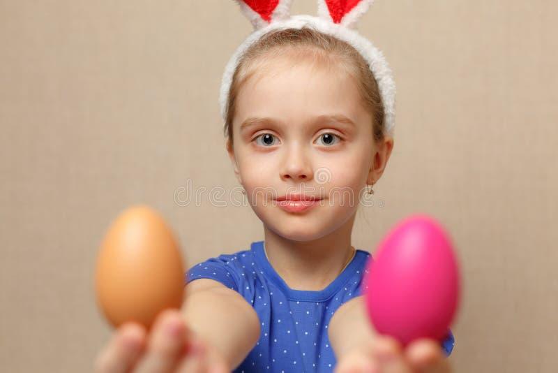 逗人喜爱的小孩女孩佩带的兔宝宝耳朵在复活节天 免版税库存图片