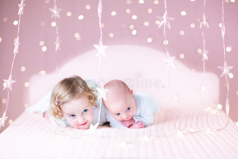 逗人喜爱的小孩女孩和她新出生的小兄弟在床上在浪漫桃红色光下 免版税库存照片