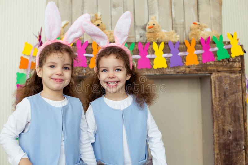 逗人喜爱的小孩女孩在复活节天孪生佩带的兔宝宝耳朵 站立在复活节装饰附近的姐妹 库存图片