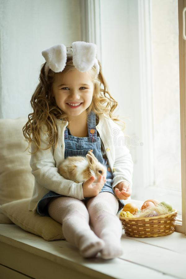 逗人喜爱的小孩女孩在拿着小的兔子的复活节天佩带兔宝宝耳朵 免版税库存图片