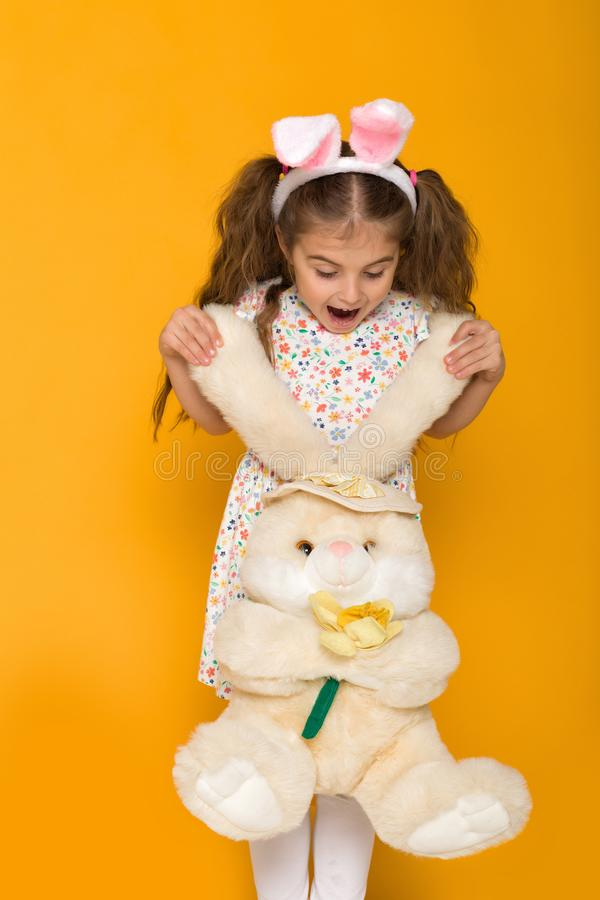 逗人喜爱的小孩女孩画象有拿着兔宝宝的复活节兔子耳朵的 免版税库存照片
