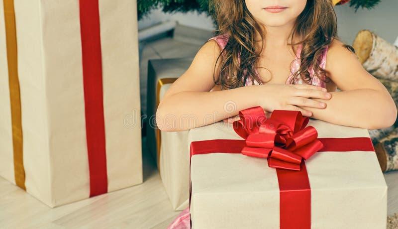 逗人喜爱的小孩女孩的Meedle部分有户内当前近的圣诞树的 免版税库存图片