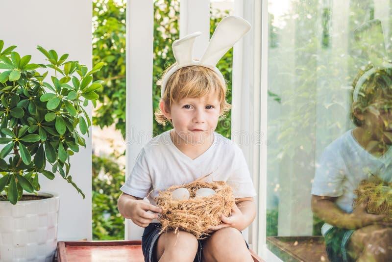 逗人喜爱的小孩男孩佩带的兔宝宝耳朵在复活节天 拿着巢用鸡蛋的男孩 库存图片