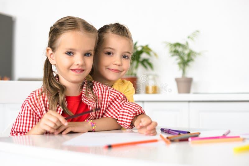逗人喜爱的小孩画象在与纸和铅笔的桌上画的 库存照片