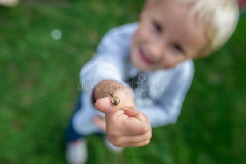 逗人喜爱的小孩顶视图有微小的蜗牛的在他的手指 免版税库存图片