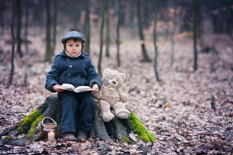 逗人喜爱的小孩,坐与他的玩具熊的一个树干 免版税库存照片