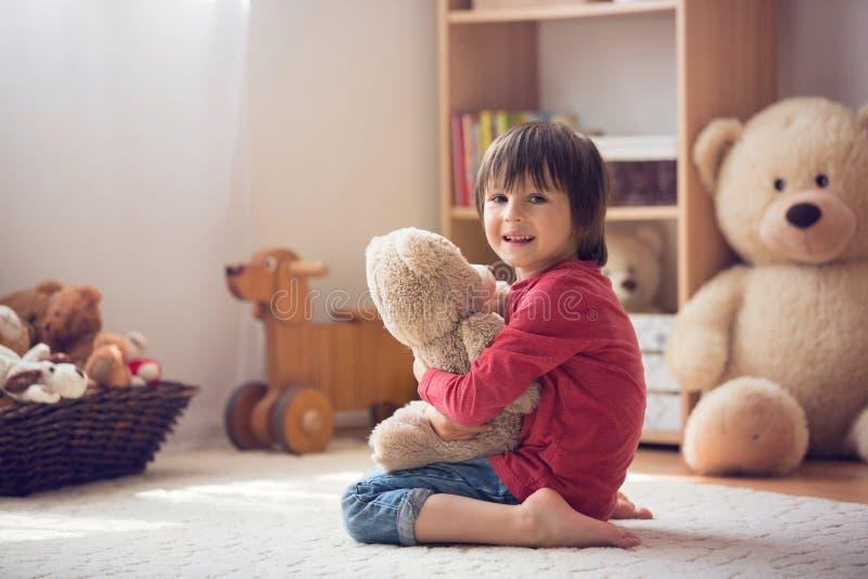 逗人喜爱的小孩,学龄前男孩,使用与玩具熊在hom 免版税库存图片