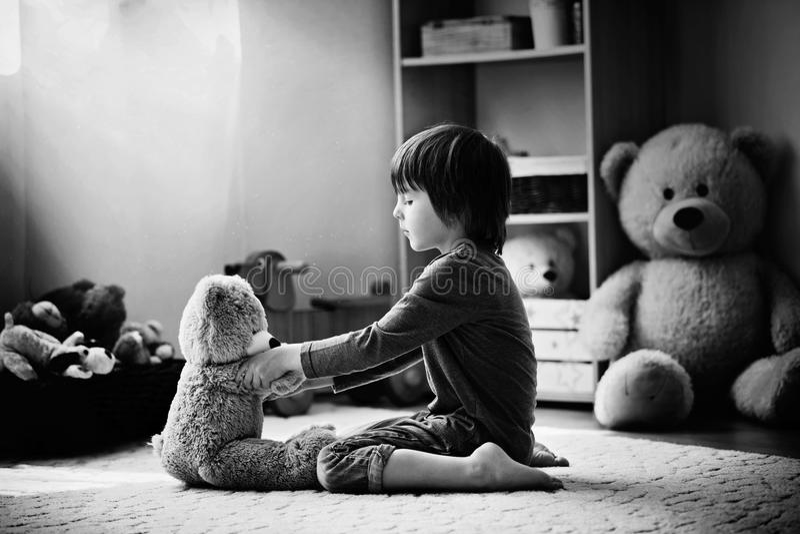 逗人喜爱的小孩,学龄前男孩,使用与玩具熊在hom 免版税图库摄影