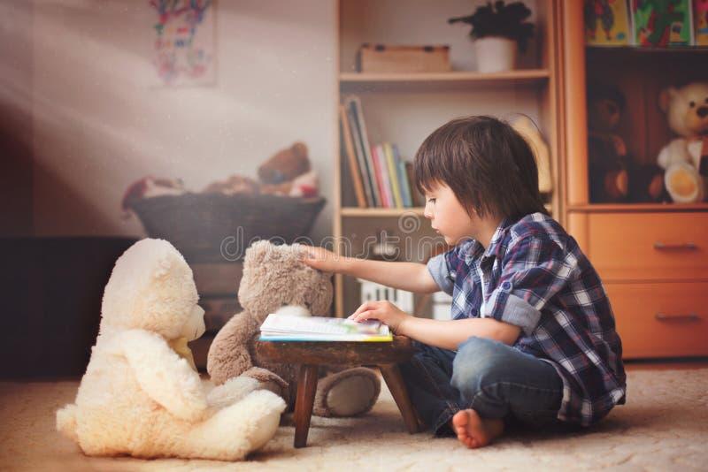 逗人喜爱的小孩,学龄前男孩,读书对他的女用连杉衬裤是 免版税库存照片
