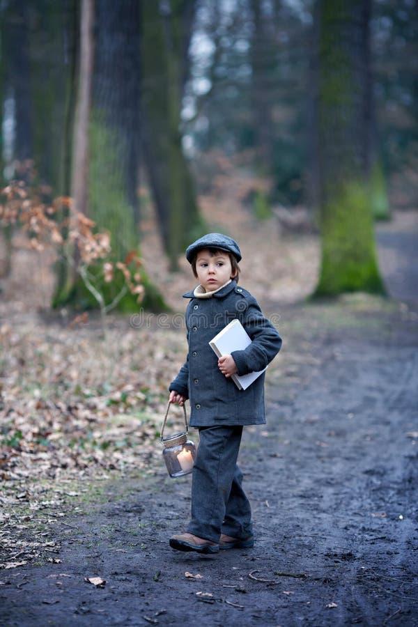 逗人喜爱的小孩,拿着灯笼和书在森林里 库存图片