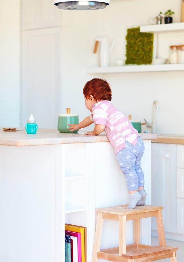 逗人喜爱的小孩婴孩在台阶凳子上升,设法到达在高书桌上的事在厨房里 图库摄影